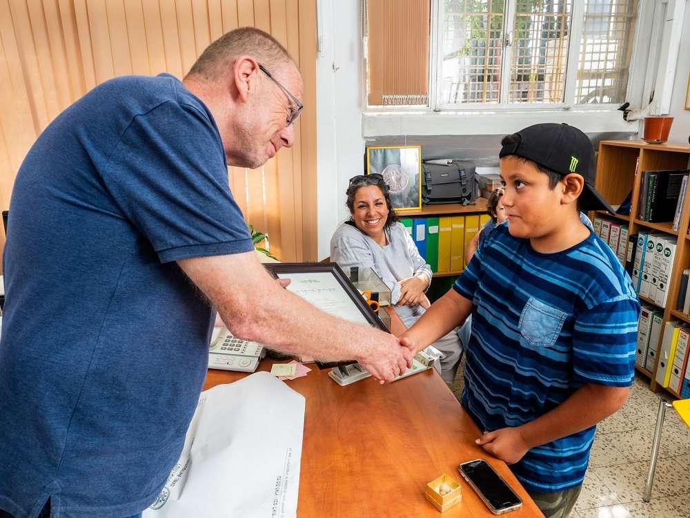 """Itamar Barnea, de 10 años, recibió un certificado de """"buena ciudadanía"""" del Dr. Zvi Greenhut de la Autoridad de Antigüedades de Israel, agosto de 2018. (Assaf Peretz / Israel Antiquities Authority)"""
