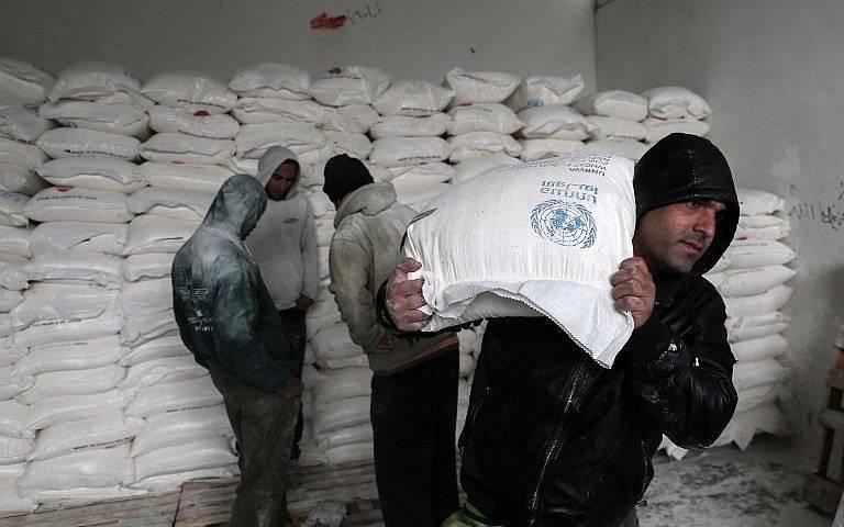 Los palestinos recogen ayuda alimentaria en un centro de distribución de alimentos de las Naciones Unidas en Khan Yunis, al sur de la Franja de Gaza, el 28 de enero de 2018. (Said Khatib / AFP)