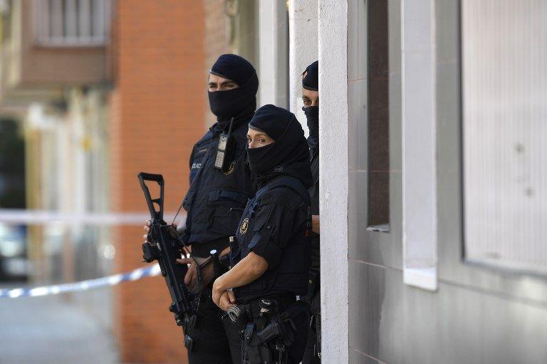 La policía regional catalana (Mossos d'Esquadra) hace guardia fuera del edificio de apartamentos de un hombre que intentó atacar una estación de policía en Cornella, cerca de la ciudad de Barcelona el noreste de España, el 20 de agosto de 2018. (LLUIS GENE / AFP)