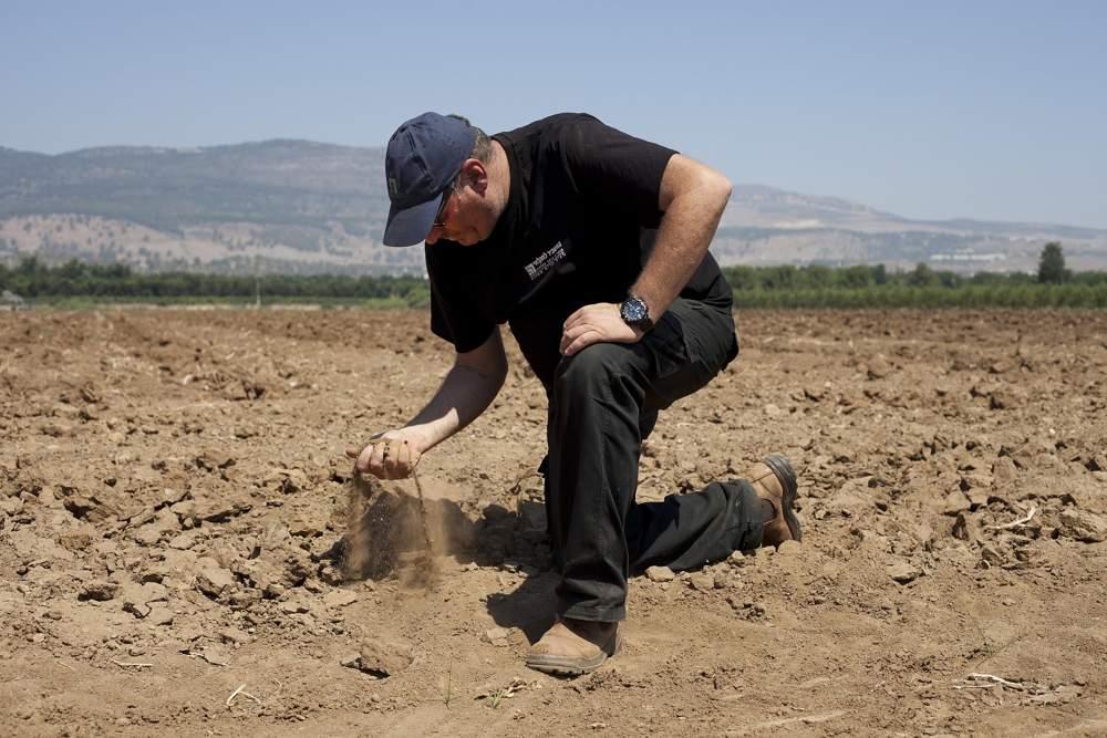 En este miércoles, 17 de julio de 2018, foto, el agricultor israelí Ofer Moskovitz revisa el suelo en su campo cerca de Kfar Yuval, Israel (AP Photo / Caron Creighton)