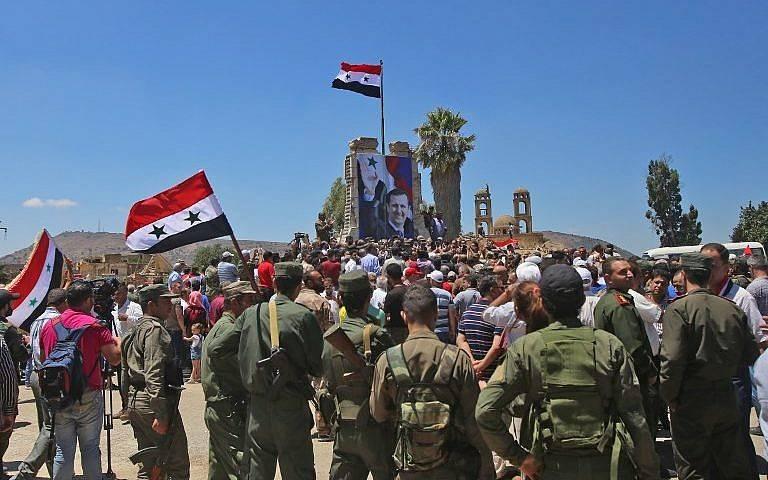 Las tropas sirias levantan la bandera siria en la ciudad fronteriza de Quneitra en los Altos del Golán sirio el 27 de julio de 2018. (AFP Photo / Youssef Karwashan)