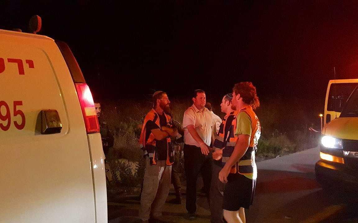 El presidente del Consejo Regional de Samaria, Yossi Dagan (2º a la izquierda) habla con paramédicos en la escena donde una mujer israelí fue atropellada y asesinada por un conductor palestino, cerca del poblado de Havat Gilad, en el norte de Samaria, el 16 de agosto de 2018. (Roi Hadi / Consejo Regional de Samaria)