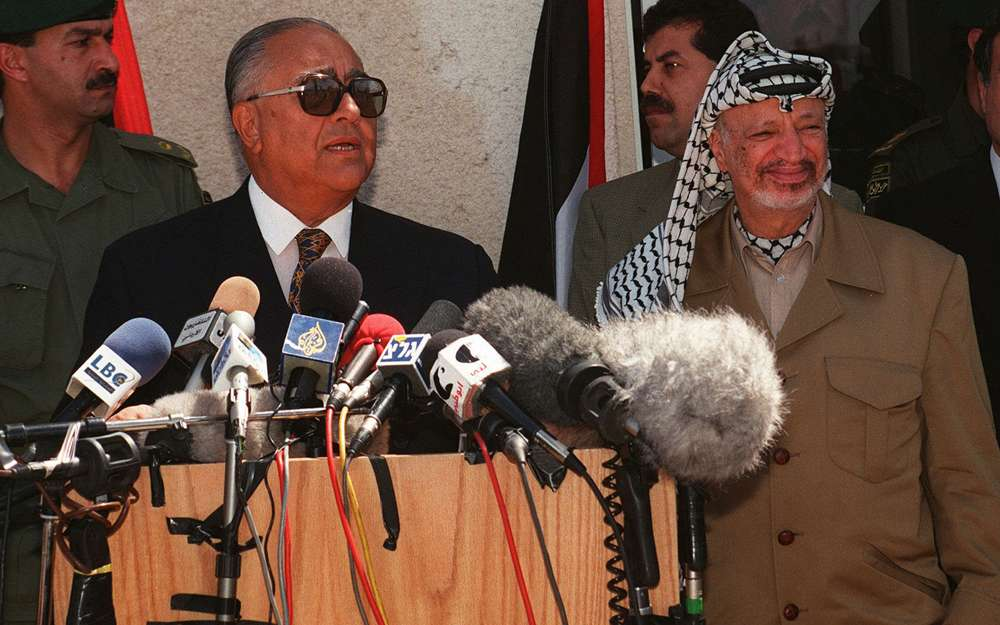 El primer ministro jordano Abdelsalam al-Majali, izquierda, habla con reporteros con el presidente de la Autoridad Palestina, Yasser Arafat, de pie junto a él durante una conferencia de prensa en Ramallah, el 20 de julio de 1997. (AP Photo / Naser Naser)