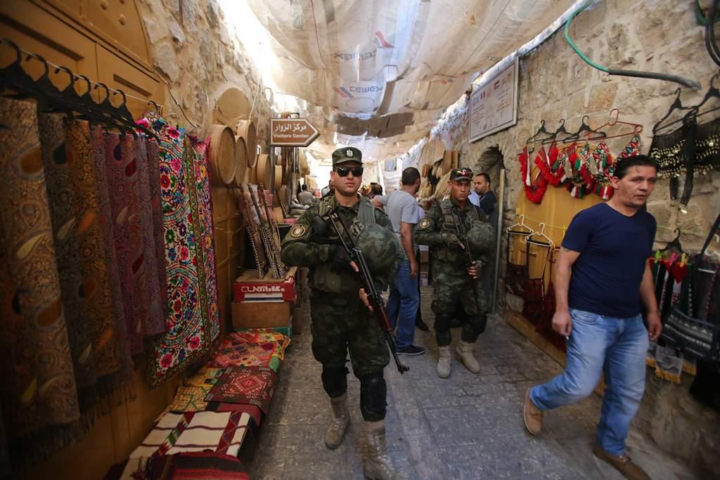 Miembros de las fuerzas de seguridad de la Autoridad Palestina caminando por la Ciudad Vieja de Hebrón (Crédito: Wafa)
