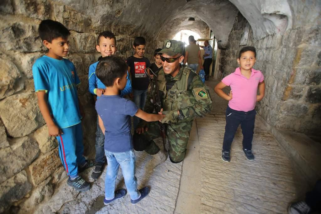 Miembro de las fuerzas de seguridad de la Autoridad Palestina interactuando con un niño en la ciudad vieja de Hebrón (Crédito: Wafa)