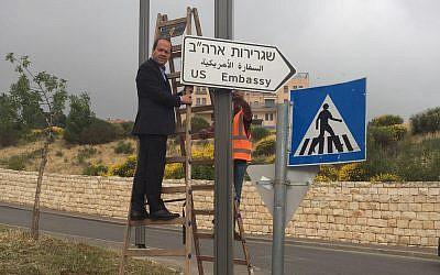 El alcalde de Jerusalem, Nir Barkat, cuelga el primer cartel que señala a la nueva embajada de los Estados Unidos en Jerusalem, el 7 de mayo de 2018 (Municipio de Jerusalem)