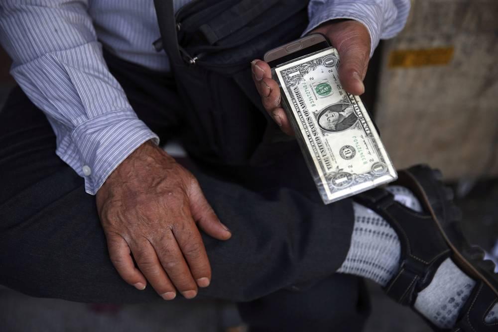 Un intercambiador de dinero callejero iraní sostiene un billete de banco estadounidense en el centro de Teherán, Irán, el 30 de julio de 2018 (AP Photo / Vahid Salemi)