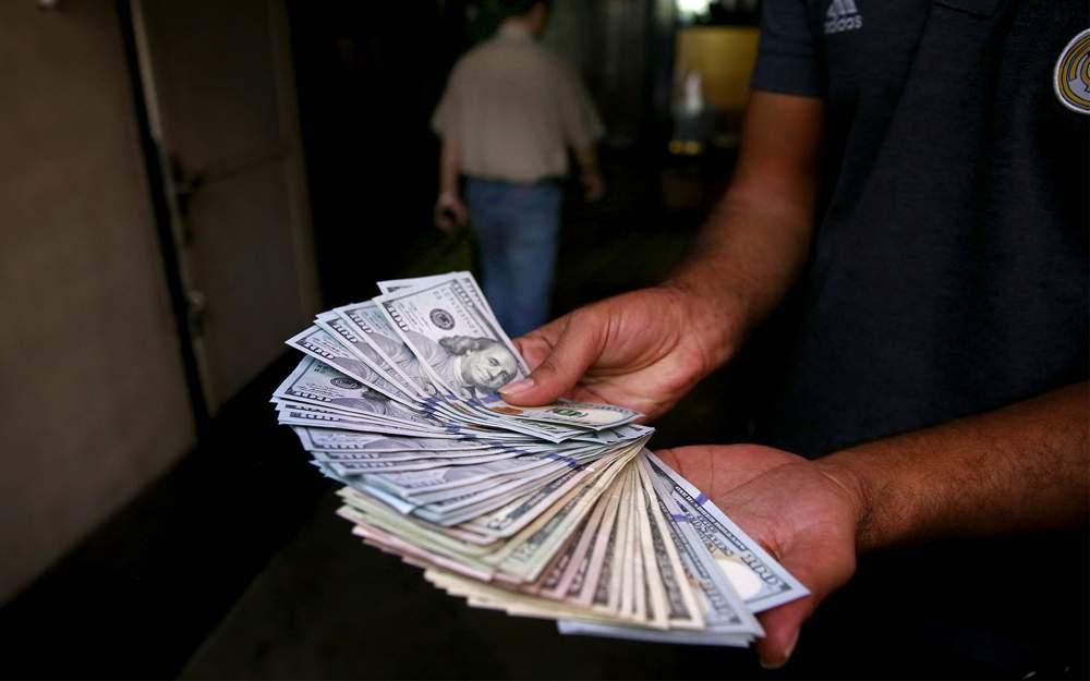 Un cambista ilegal de dinero en la calle posa con sus billetes de los Estados Unidos en el centro de Teherán, Irán, el martes 7 de agosto de 2018. (AP Photo / Ebrahim Noroozi)