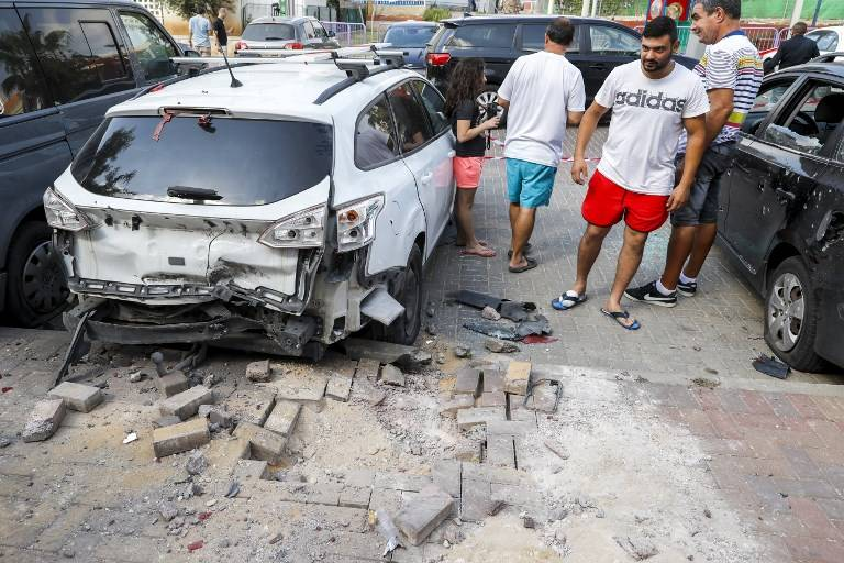 Hombres israelíes junto a un automóvil que resultó dañado después de que un cohete lanzado por terroristas de la Franja de Gaza cayó en la ciudad de Sderot, al sur de Israel, el 9 de agosto de 2018. (AFP PHOTO / JACK GUEZ)