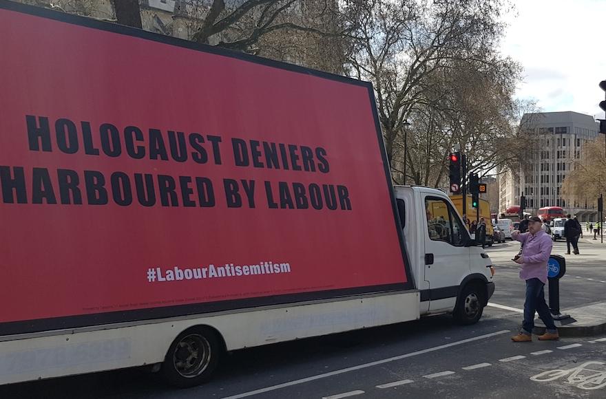 Keith Walker involucra al conductor de una furgoneta que transporta una cartelera sobre el antisemitismo en el Partido Laborista en la Plaza del Parlamento de Londres, el 17 de abril de 2018. (Cnaan Liphshiz / JTA)
