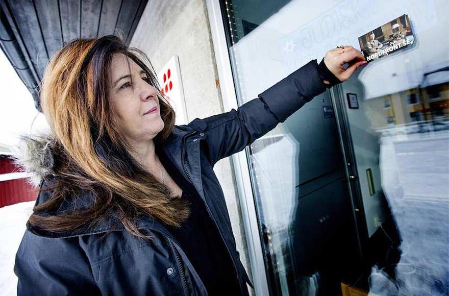 Carinne Sjoberg pelando una pegatina que los neonazis dejaron en la puerta de lo que solía ser el centro comunitario judío de Umea, Suecia.(Cortesía de Sjoberg / vía JTA)