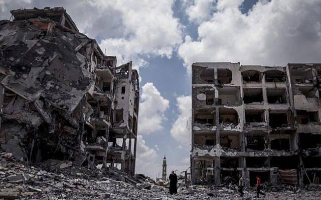 Los palestinos caminan frente a edificios destruidos por el ejército israelí en la ciudad de Beit Lahiya, al norte de la Franja de Gaza, el lunes 4 de agosto de 2014. (Emad Nasser / Flash90)