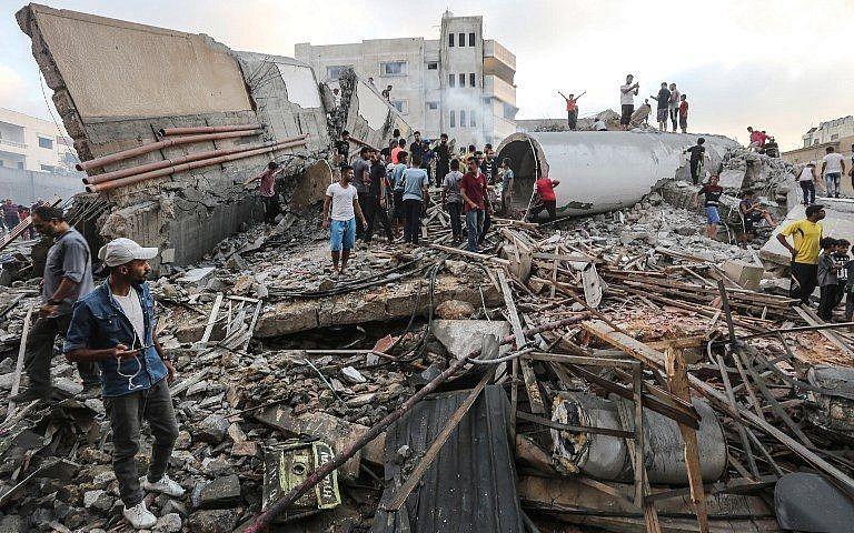 Una fotografía tomada el 9 de agosto de 2018 muestra a personas inspeccionando los escombros de un edificio atacado por la Fuerza Aérea israelí en respuesta a un ataque con cohetes que azotó el sur de Israel el 9 de agosto de 2018. (AFP Photo / Mahmud Hams)