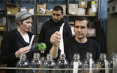 Ilustrativo: un trabajador palestino habla con su empleado judío en la fábrica SodaStream en el parque industrial Mishor Adumim, 2 de febrero de 2014. (Crédito de la foto: Nati Shohat / Flash90)