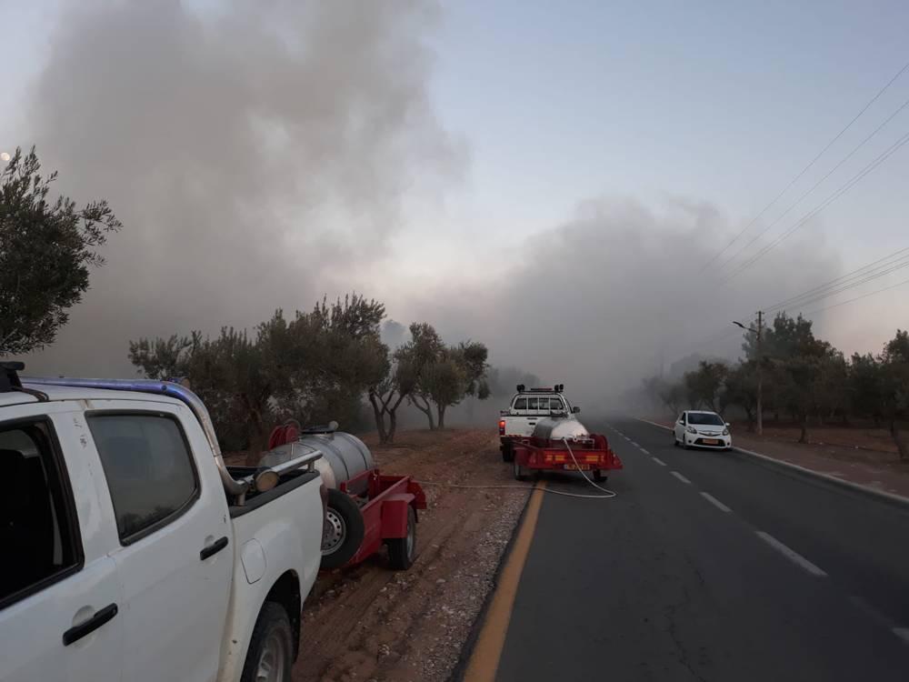 Los oficiales de seguridad locales trabajan para apagar un incendio, provocado por globos incendiarios de la Franja de Gaza, en el área de Hevel Shalom, en el sur de Israel, el 26 de junio de 2018. (Seguridad Eshkol)
