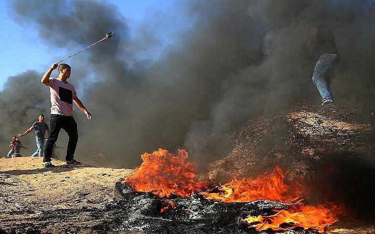 Islamista palestino utiliza un tirachinas durante los enfrentamientos a lo largo de la frontera entre Israel y la Franja de Gaza, en la ciudad de Khan Younis, al sur de Gaza, el 10 de agosto de 2018. (AFP Photo / Said Khatib)