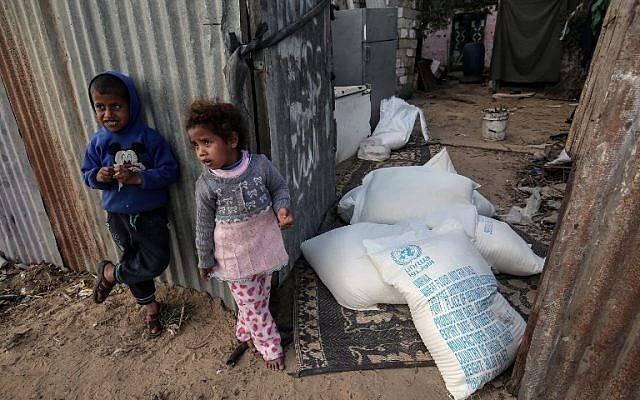 Niños palestinos se ponen de pie junto a bolsas de ayuda alimentaria proporcionadas por la agencia de la ONU para refugiados palestinos en el campo de refugiados de Rafah en el sur de la Franja de Gaza el 24 de enero de 2018. (AFP Photo / Said Khatib)