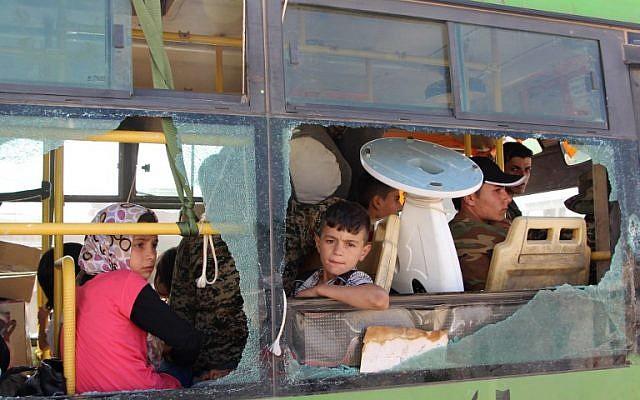Imagen ilustrativa de los sirios evacuados del área de Fuaa y Kafraya en la provincia de Idlib, mirando por la ventana de un autobús roto durante la evacuación de varios miles de residentes de las dos ciudades pro régimen en el norte de Siria el 19 de julio de 2018. (AFP / STR)