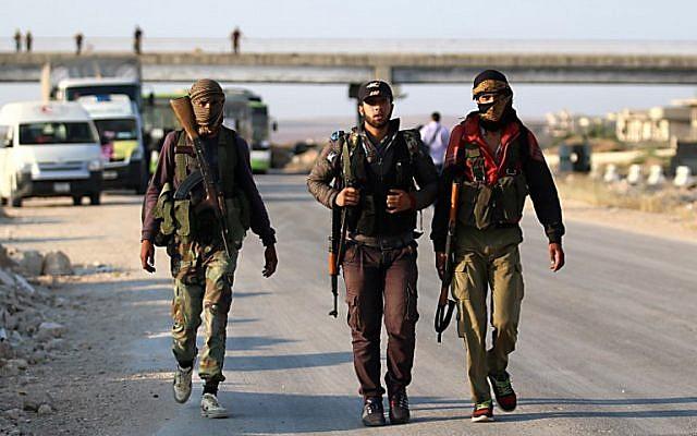 Los combatientes rebeldes sirios de la provincia de Quneitra caminan con sus rifles mientras esperan en el punto de cruce de Morek para ser transferidos en las provincias de Idlib y Aleppo el 21 de julio de 2018. (AFP Photo / Aaref Watad)