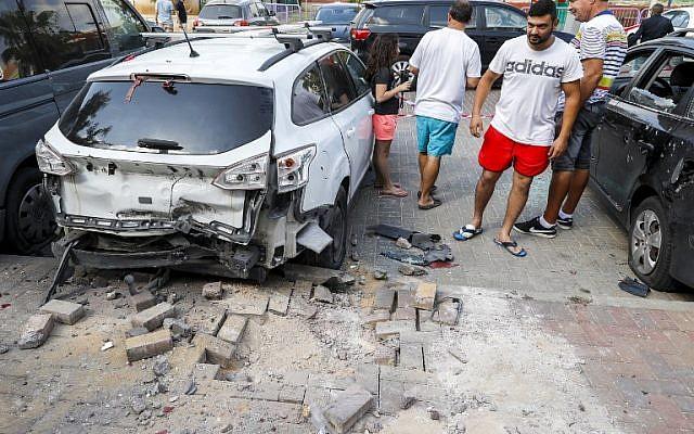 La gente se para junto a un automóvil que resultó dañado después de que un cohete disparado por terroristas de la Franja de Gaza cayó en la ciudad de Sderot, al sur de Israel, el 9 de agosto de 2018. (JACK GUEZ / AFP)