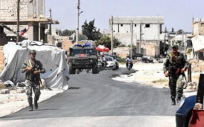 Las fuerzas sirias y rusas montan guardia mientras los civiles entran en el cruce de Abu Duhur en el extremo oriental de la provincia de Idlib, el 20 de agosto de 2018. (AFP / George Ourfalian)