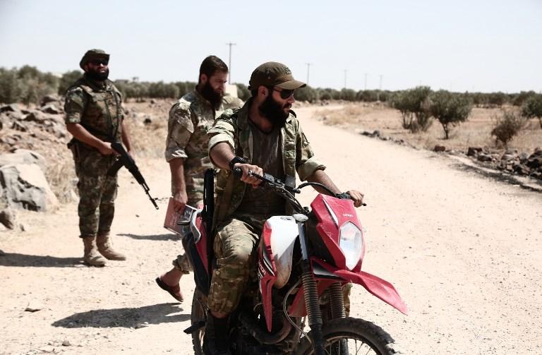 """Los combatientes rebeldes sirios del recientemente formado """"Frente de Liberación Nacional"""" refuerzan una posición en el frente cerca de la aldea de Abu Dali en el campo de la provincia de Idlib el 1 de septiembre de 2018, anticipándose a la inminente ofensiva de las fuerzas gubernamentales. (AFP PHOTO / Nazeer AL-KHATIB)"""