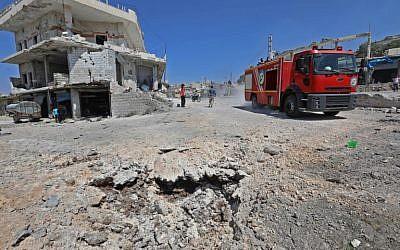 Una foto tomada el 4 de septiembre de 2018 muestra un recorrido de un camión de bomberos por una carretera dañada después de un ataque aéreo ruso en la ciudad de Muhambal, a unos 30 kilómetros al suroeste de la ciudad de Idlib. (AFP / Omar Haj Kadour)