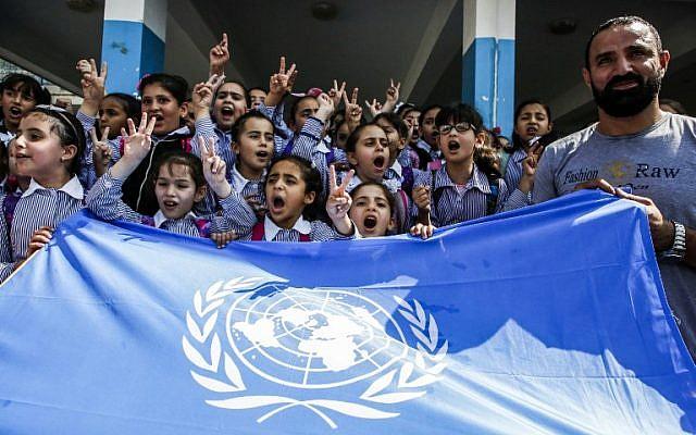 Los escolares palestinos gritan consignas y levantan el gesto de victoria sobre una bandera de la ONU durante una protesta en una escuela de la Agencia de Socorro y Obras de las Naciones Unidas (UNRWA), financiada por US AID, en el campamento de refugiados de Arroub cerca de Hebrón en Cisjordania el 5 de septiembre. 2018. (AFP / Hazem Bader)