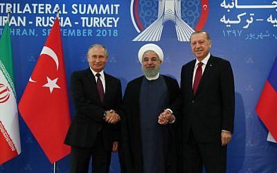 Una foto impresa tomada y publicada el 7 de septiembre de 2018 por el servicio de Prensa Presidencial de Turquía muestra al presidente turco Recep Tayyip Erdogan (R), al presidente iraní Hassan Rouhani (C) y al presidente ruso Vladimir Putin (L) uniéndose en una cumbre trilateral en Teherán . (Oficina de prensa de la Presidencia turca / AFP)