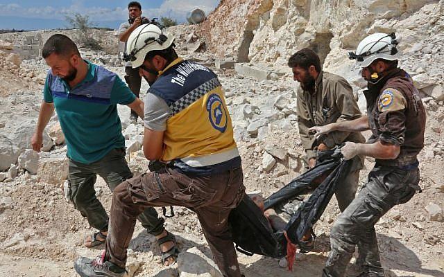 """Esta fotografía tomada en Kafr Ain el 7 de septiembre de 2018 muestra a miembros de la Defensa Civil siria, también conocidos como los """"Cascos Blancos"""", llevando a una víctima después de los ataques aéreos, a cuatro kilómetros al este de Khan Shaykhun en el campo meridional de la provincia de Idlib. (AFP / Anas Al-Dyab)"""