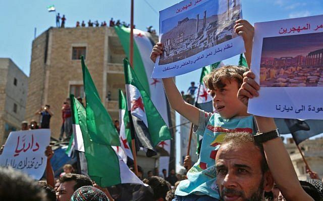 Los manifestantes sirios agitan su bandera nacional mientras se manifiestan contra el régimen y su aliado Rusia, en la ciudad de Idlib, controlada por los rebeldes, el 7 de septiembre de 2018. (AFP / Zein Al Rifai)
