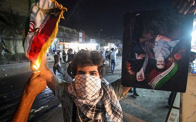 Un manifestante iraquí sostiene una bandera iraní mientras otra le prendió fuego, junto a un retrato que representa a los antiguos y actuales líderes supremos, los ayatolá Jomeini y Jamenei, durante las manifestaciones contra el gobierno y la falta de servicios básicos en Basora el 7 de septiembre de 2018. (AFP Photo / Haidar Mohammad Ali)