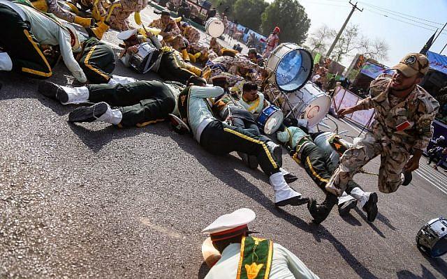 Un soldado iraní pasa corriendo junto a sus colegas heridos que yacen en el suelo en la escena de un ataque a un desfile militar en Ahvaz, el 22 de septiembre de 2018. (AFP / ISNA / MORTEZA JABERIAN)