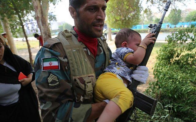 Una imagen puesta a disposición por la agencia iraní Mehr News el 22 de septiembre de 2018 muestra a un soldado iraní que portaba un niño en el sitio de un ataque a un desfile militar en la ciudad iraní de Ahvaz, que conmemoraba el aniversario del estallido de su devastadora guerra de 1980-1988 con el Iraq de Saddam Hussein. (AFP / MEHR NOTICIAS Y AFP PHOTO / Mehdi Pedramkhou)