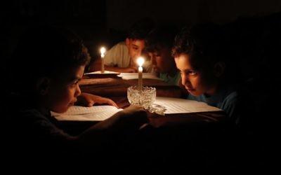 Niños palestinos en casa leyendo libros a la luz de las velas debido a la escasez de electricidad en la ciudad de Gaza, 13 de junio de 2017. (AFP / Thomas Coex)