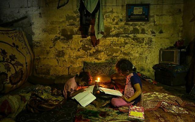 Ilustrativo: los niños palestinos hacen sus deberes a la luz de las velas durante un corte de energía en la ciudad de Gaza el 11 de septiembre de 2017. (AFP Photo / Mahmud Hams)