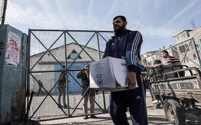 Los refugiados palestinos recogen paquetes de ayuda en un centro de distribución de alimentos de las Naciones Unidas en Rafah, en el sur de la Franja de Gaza, el 21 de enero de 2018. (AFP / Said Khatib)