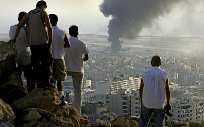 En esta foto del 14 de julio de 2006, jóvenes libaneses se reúnen en la cima de una colina con vistas a la ciudad de Beirut en el Líbano al atardecer para ver cómo el humo sigue volando desde un depósito de combustible en el Aeropuerto Internacional de Beirut, que fue golpeado por un ataque aéreo israelí. (Foto AP / Ben Curtis)
