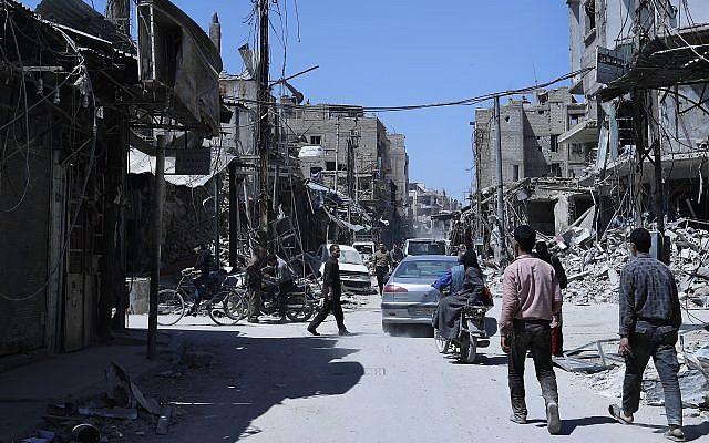 La gente camina entre edificios dañados en la ciudad de Douma, donde se sospecha un ataque con armas químicas, cerca de Damasco, Siria, el 16 de abril de 2018. (AP Photo / Hassan Ammar)