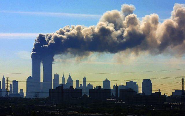 ARCHIVO - En esta foto de archivo del 11 de septiembre de 2001, vista desde la autopista New Jersey Turnpike, cerca de Kearny, Nueva Jersey, se filtraron nubes de humo desde las torres gemelas del World Trade Center en Nueva York después de que los aviones se estrellaran en ambas torres. (Foto AP / Gene Boyars, Archivo)
