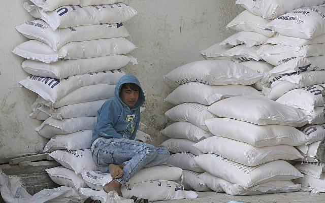 Un palestino se sienta en sacos de harina mientras espera recibir ayuda alimentaria del centro de distribución de alimentos de la ONU en el campo de refugiados de Nusseirat, en el centro de la Franja de Gaza, el 17 de enero de 2018. (AP Photo / Adel Hana)