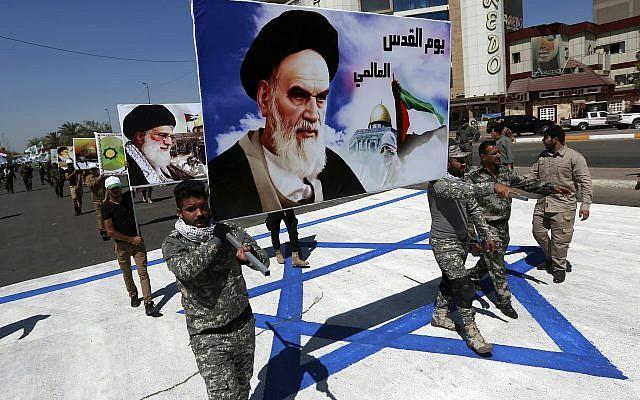 En esta foto de archivo del 23 de junio de 2017, los partidarios de las brigadas iraquíes de Hezbollah, respaldadas por Irán, marchan sobre una representación de una bandera israelí con un retrato del fallecido líder iraní Ayatolá Jomeini y el líder supremo de Irán, el ayatolá Ali Jamenei, en Bagdad, Irak. (AP / Hadi Mizban)