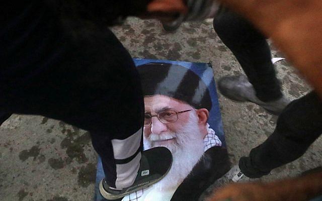 Los manifestantes pisotean un retrato del líder supremo de Irán, el ayatolá Ali Khamenei, durante el asalto y la quema del consulado iraní en la ciudad de Basora, al sur de Irak, el 7 de septiembre de 2018. (AP / Nabil al-Jurani)