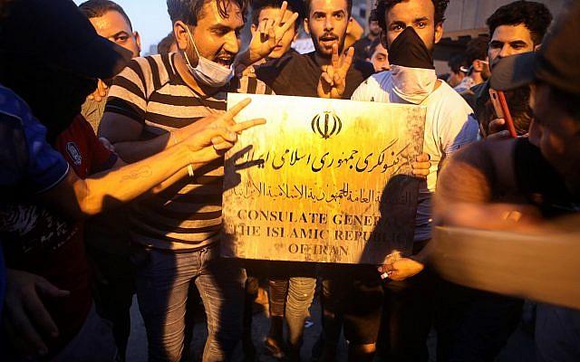 Los manifestantes sostienen un letrero perteneciente al edificio del consulado iraní antes de asaltar y quemar el consulado iraní en la ciudad de Basora, al sur de Irak, el 7 de septiembre de 2018. (AP / Nabil al-Jurani)