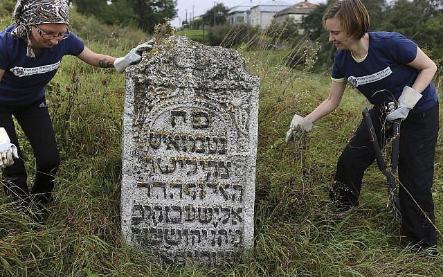 En esta foto tomada el 29 de agosto de 2018, los voluntarios limpian un antiguo cementerio judío en Rohatyn, el sitio de un proyecto de Herencia Judía, cerca de Lviv, Ucrania. (Foto AP / Yevheniy Kravs)