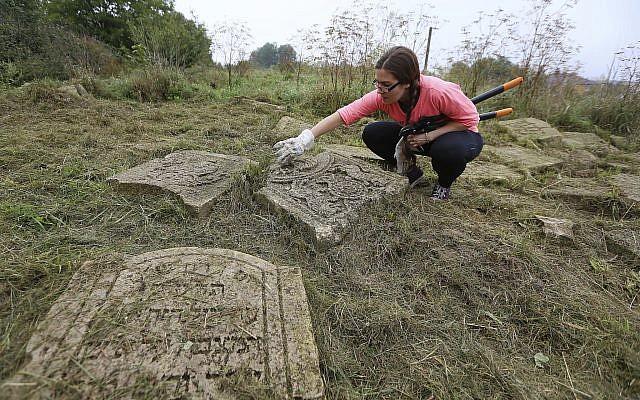 En esta foto tomada el 29 de agosto de 2018, un voluntario limpia un antiguo cementerio judío en Rohatyn, el sitio de un proyecto de herencia judía, cerca de Lviv, Ucrania. (Foto AP / Yevheniy Kravs)