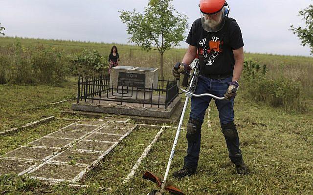 En esta foto tomada el 29 de agosto de 2018, Jay Osborn, un líder del proyecto de herencia judía de Rohatyn, limpia un antiguo cementerio judío en Rohatyn, el sitio de un proyecto de herencia judía, cerca de Lviv, Ucrania. (Foto AP / Yevheniy Kravs)