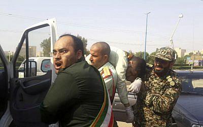 Miembros de la Guardia Revolucionaria llevan a un compañero herido después de un tiroteo durante su desfile por el 38 aniversario de la invasión de Irán en 1980, en la ciudad suroccidental de Ahvaz, Irán, 22 de septiembre. 2018. (AP Photo / ISNA, Shayan Haji Najaf)