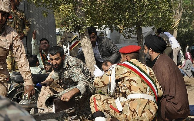 En esta foto proporcionada por la Agencia de Noticias de Estudiantes Iraníes, ISNA, miembros de las fuerzas armadas iraníes y civiles se refugian en un tiroteo durante un desfile militar que conmemora el 38 aniversario de la invasión de Irán en 1980, en la ciudad suroccidental de Ahvaz, Irán, septiembre 22, 2018. (AP Photo / ISNA, Behrad Ghasemi)