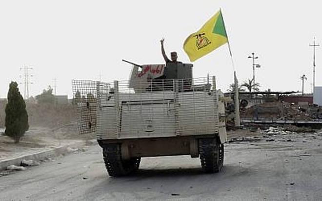 En esta foto del miércoles 27 de mayo de 2015, un combatiente de un vehículo blindado perteneciente a la Brigada chiita de Hizbollah, respaldada por Irán, ondea un v-sign mientras patrulla al este de Ramadi, Iraq. (AP)